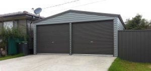 Double steel garage in horizontal M cladding with roller doors by Judds Garages