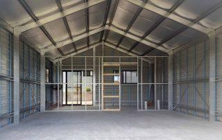 Double garage with single 5-metre roller door showing internal wall of rear room