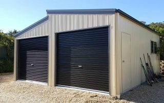 Double monopitch garages in vertical K panel cladding near Belmont